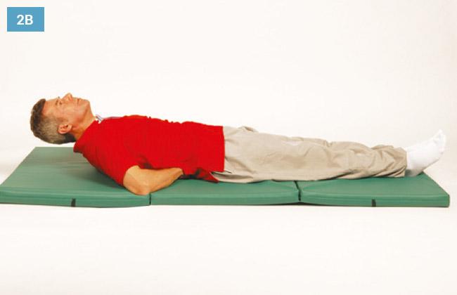Ćwiczenie w leżeniu na plecach z wyprostowanymi kolanami stopy na materacu i dłonie pod kręgosłupem