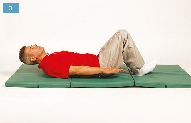 Ćwiczenie w leżeniu na plecach, głowa uniesiona, ręce nad materacem, piety oparte o materac