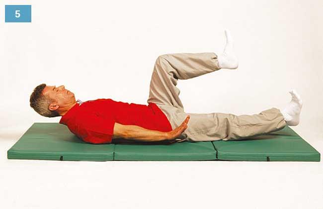 Ćwiczenie w leżeniu na plecach, głowa uniesiona, nogi nad materacem, jedna zgięta druga wyprostowana