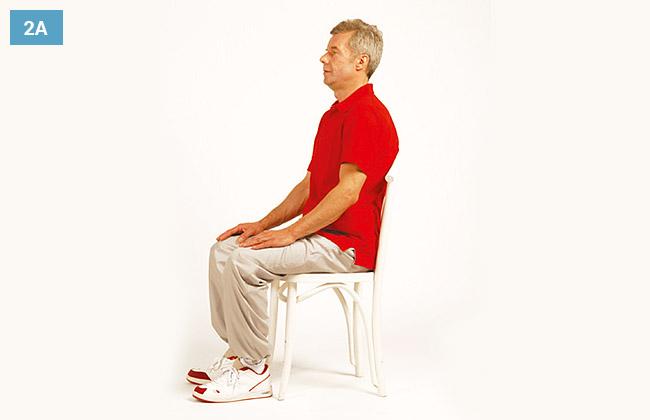 Ćwiczenie w siadzie na krześle, ręce oparte na kolanach, pochylona głowa do przodu
