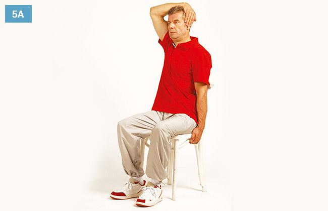Ćwiczenie w siadzie na krześle, prawa ręka chwyta za przeciwległe ucho